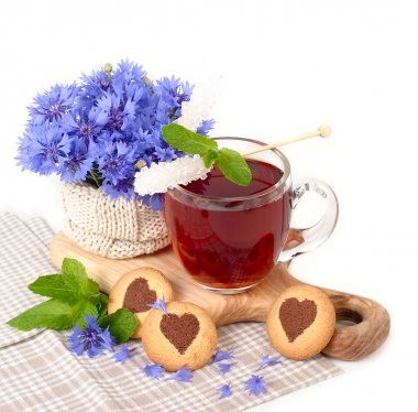 Black tea in a transparent mug with cornflowers and mint and cookies in the form of heart on a white background.