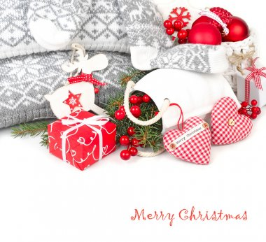 Christmas composition with red textile hearts, a red gift box and Christmas-tree decorations in the Scandinavian style on a white background. A Christmas background with a place for the text.