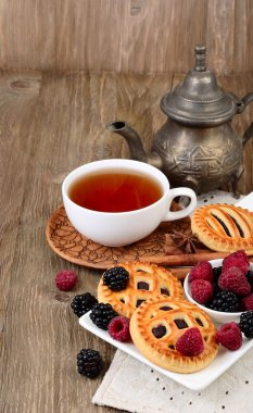 Cup of black tea, berry cookies and fresh raspberry and blackberry on a dark wooden background. Vertical format.