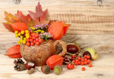 Autumn background with leaves, chestnuts and a mountain ash with a place for the text. Autumn composition on a wooden background.