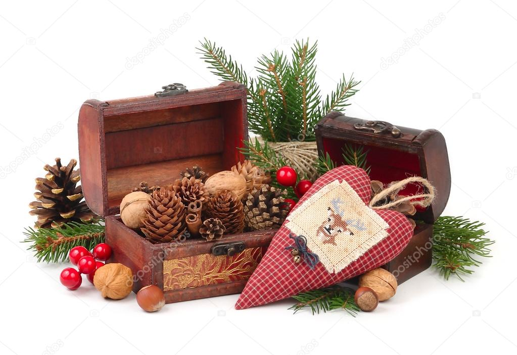 Wooden chests with cones and nuts and textile checkered heart with a deer on branches of a Christmas tree on a white background. A Christmas background with a place for the text.