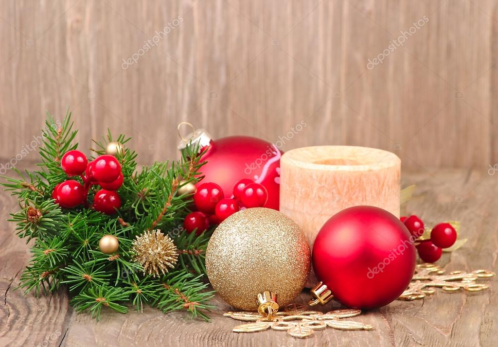 Christmas composition with Christmas balls, a candle and branches of a Christmas tree on a wooden background with a place for the text.