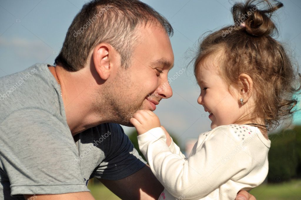 Happy father with his daughter outdoors hugging together