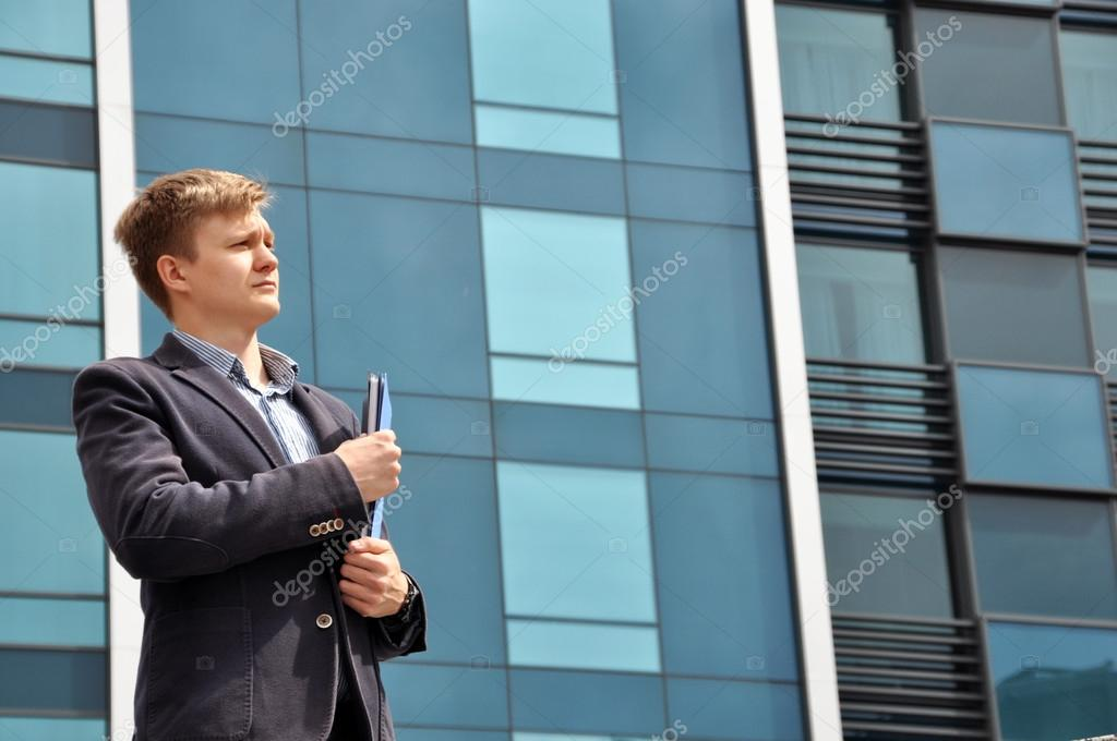 Businessman with a folder on the background of glass