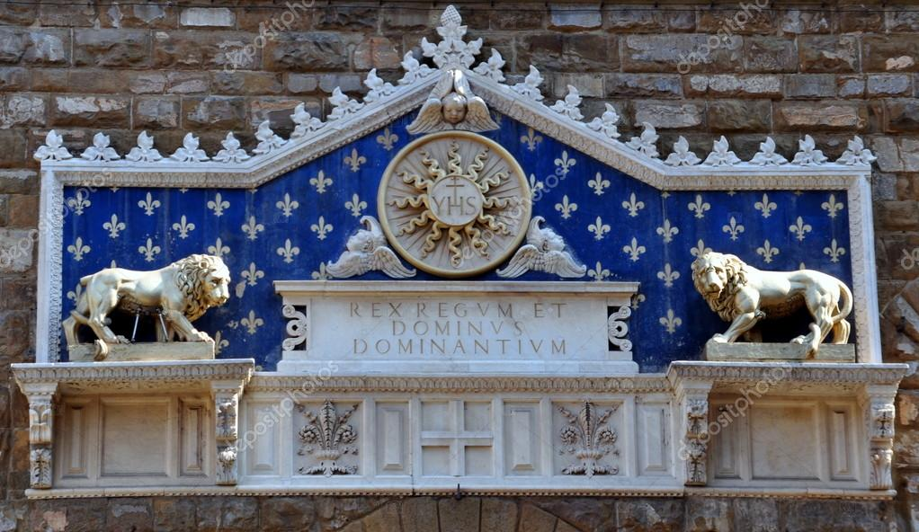 Medallion with the monogram of Christ between two lions above The Palazzo Vecchio is town hall of Florence, Italy.