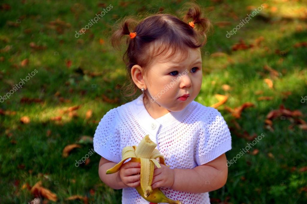 Девушка ест банан стоковое изображение. изображение
