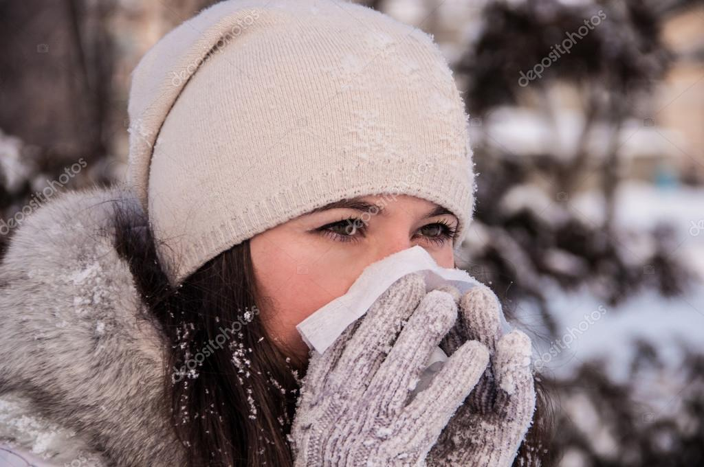Girl with handkerchief has the flu and running nose winter