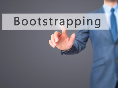 Bootstrapping - Businessman hand pressing button on touch screen