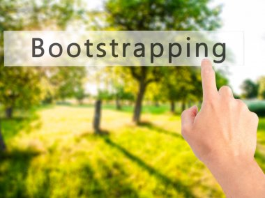 Bootstrapping - Hand pressing a button on blurred background con
