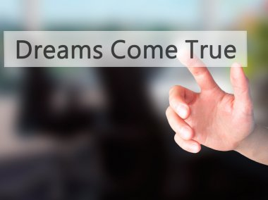 Dreams Come True - Hand pressing a button on blurred background