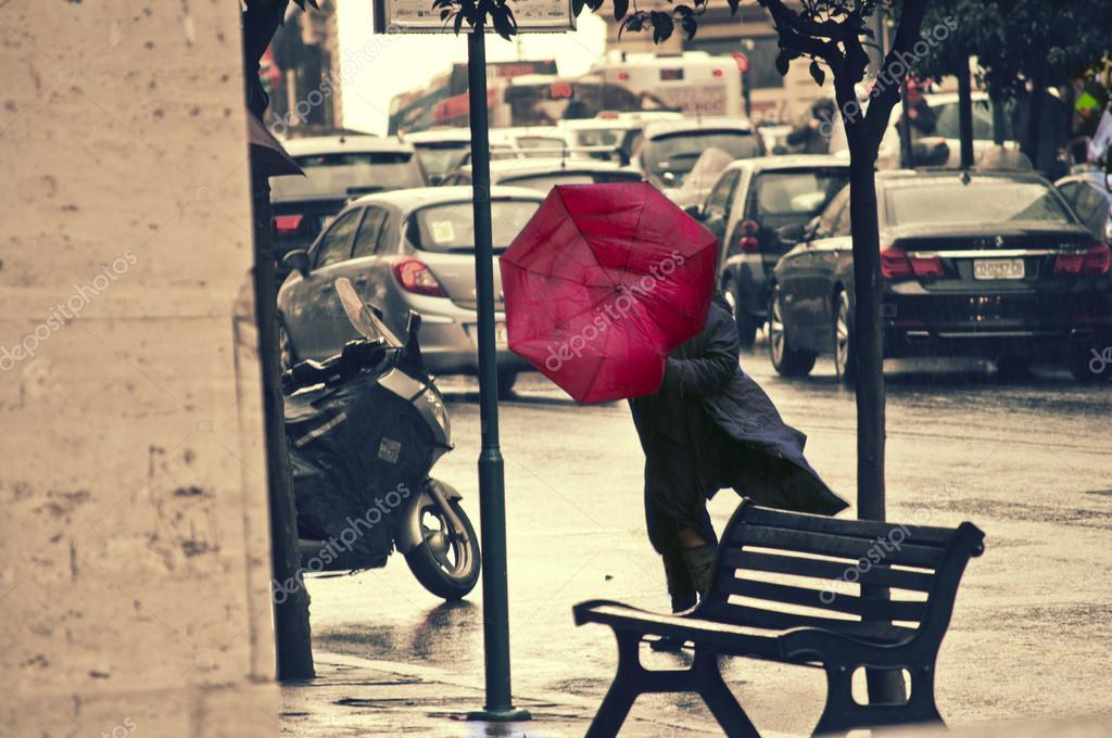 People rushing on the windy rainy street. Red Umbrella