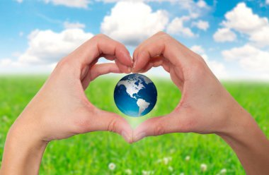 Hands holding green globe with grassy background - Stock Image