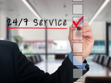 Businessman Checking 24h Service. Checking mark on checklist marker. Isolated on blue background, Stock Photo