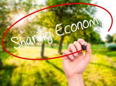 Man Hand writing Sharing Economy with black marker on visual scr