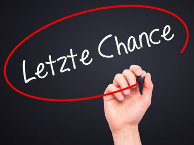 Man Hand writing Letzte Chance  (Last Chance in German) with bla