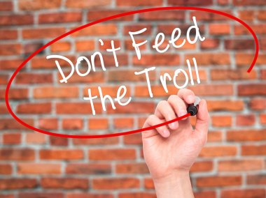Man Hand writing Don't Feed the Troll with black marker on visua