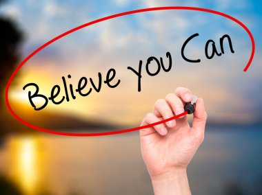 Man Hand writing Believe you Can with black marker on visual scr