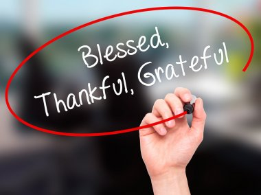 Man Hand writing  Blessed Thankful Grateful with black marker on