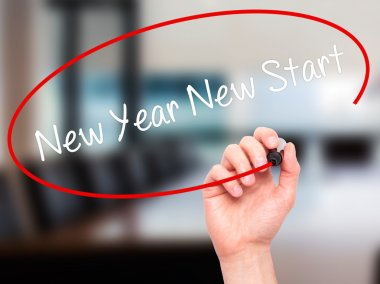 Man Hand writing New Year New Start with black marker on visual