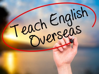 Man Hand writing Teach English Overseas with black marker on vis
