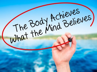 Man Hand writing The Body Achieves What the Mind Believes with b