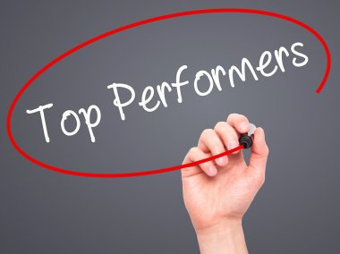 Man Hand writing Top Performers with black marker on visual scre