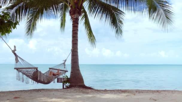 Žena v houpací síti na pláži. Přiblížit
