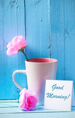 Mug with pink roses on blue wood background with good morning text