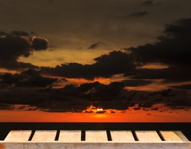 Old wood table and  dust cloud and red sunset background with a dark color tone  gray to orange gradient  over the ocean.