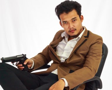 Businessman bodyguard on brown suit holding the gun