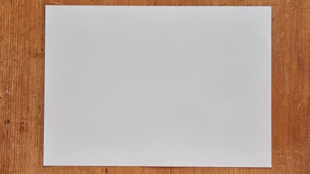 Papírgömb kibontása. Állítsa le a mozgó animáció egy kibontakozó papírlabda egy fa asztalon. Gyűrött papír bontakozik ki stop motion.