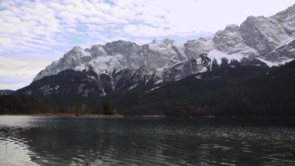 Odrážející se horské jezero s ostrůvky před zasněženými horami v německých Alpách. Panorama odrazného horského jezera.
