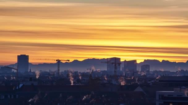 Zeitraffer bei Sonnenaufgang in München mit Blick auf die Alpen. Stadt vor einer Bergsilhouette bei Sonnenaufgang.