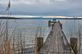 Altes hölzernes Dock in einem See. Alter Holzsteg umgeben von Schilf in einem Bergsee.