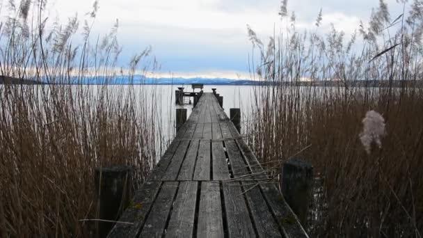 Altes hölzernes Dock in einem Bergsee. Alter Holzsteg umgeben von beweglichem Schilf in einem Bergsee.