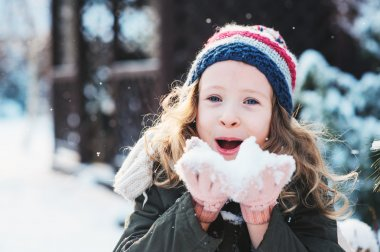 happy child girl playing with snow on snowy winter walk