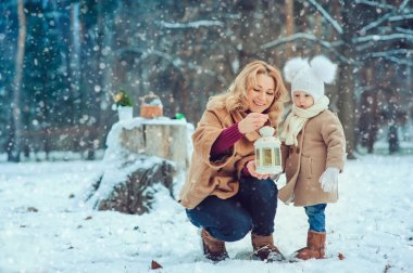 Happy mother and baby daughter walking in snowy winter park. Christmas family time.