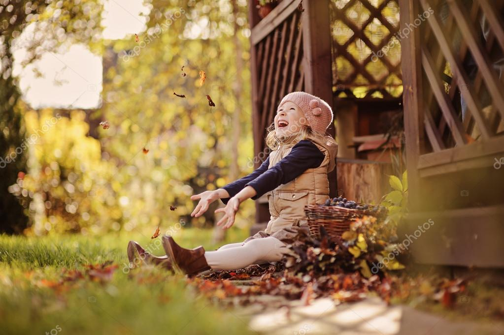 Cute happy child girl playing and throwing leaves in sunny autumn garden