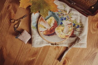 Beautiful cross stitch autumn design with mushrooms in process on wooden table with scissors