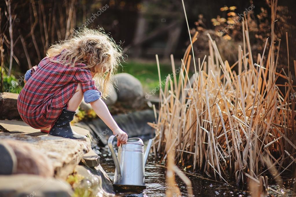 Child girl in plaid dress gathering water from pond in spring garden