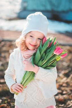 Spring portrait of happy child girl with tulips bouquet for woman's day