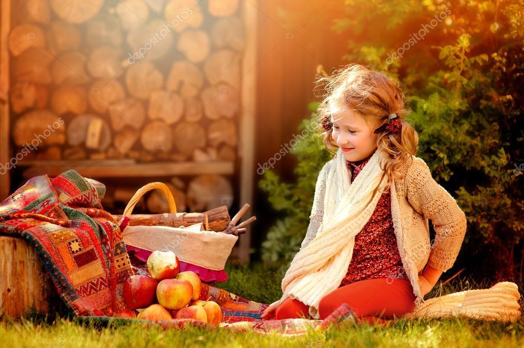 chica de niño feliz de bufanda hecha punto blanca con manzanas rojas ...