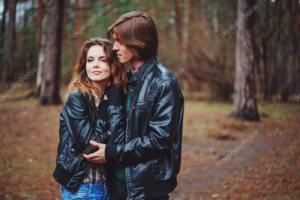 happy loving couple in leather jackets walking outdoor. Young boyfriend and girlfriend hugs and kissing in the forest