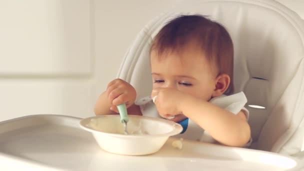 Roztomilá holčička, která jí dětskou stravu lžící. její obličej je potřísněn jogurtem na vysoké židli v domácí kuchyni