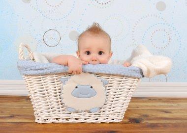 Handsome baby boy peeking out of wicker basket