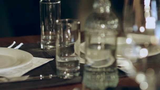 Číšník klade na stolním vínem brýle