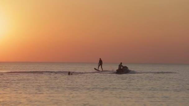 Muž balancují na Hoverboard přes vodu na slunce pozadí