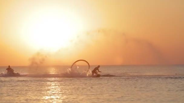 Silueta muže baví na Flyboard v moři při západu slunce pozadí