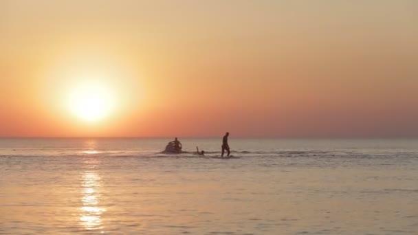 Muž na to Hoverboard bude se přijít z moře na břeh. Západ slunce
