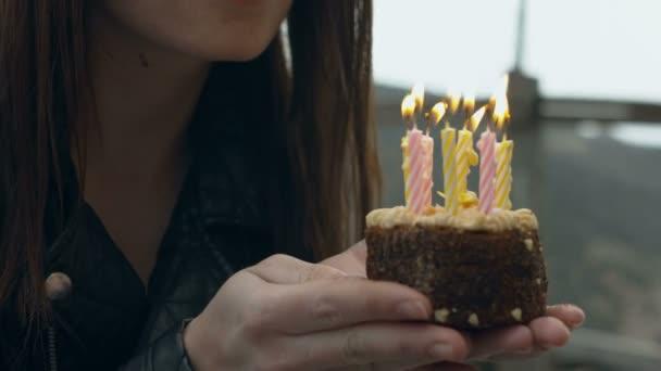 lány fúj a gyertyákat a tortán